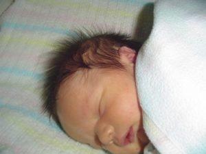 У новорожденного много волос на голове